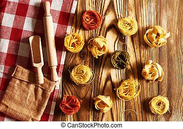 Pasta tagliatelle set over wooden background