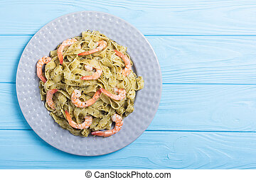 Pasta tagliatelle with sauce pesto and shrimps