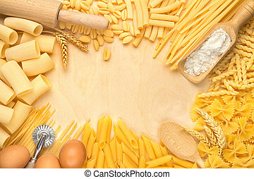pasta types and kitchen utensils on wooden table
