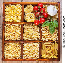 Pasta variety in a compartmented box with garlic, tomatoes and basil