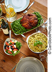 pasta, vegetable salad and roast chicken on table