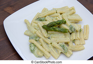 Pasta with cream of asparagus on wooden table close up view