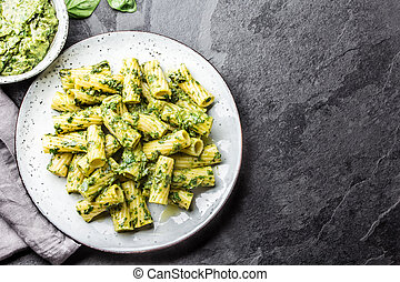Pasta with green avocado herbs sauce. Top view, on slate