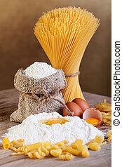 Pasta with ingredients - flour and eggs on old wooden table