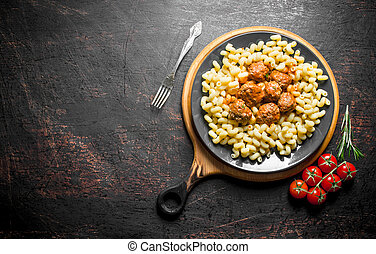 Pasta with meat balls and tomatoes on a branch.