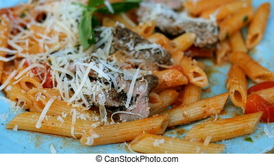 Pasta with savory tomato sauce, meat, parmesan and tomatoes is eaten with a fork with blue plate.