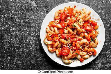 Pasta with tomato slices on a plate.