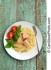 Pasta with tomatoes, green basil and salmon filet in white plate on turquoise background