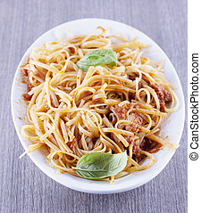 Pasta with tuna and basil, white plate, gray wood, vertical...