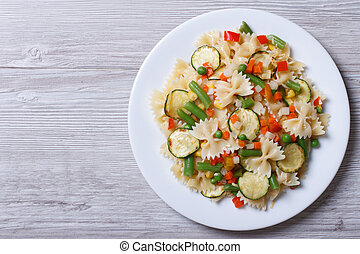 pasta with vegetables on a wooden background. top view