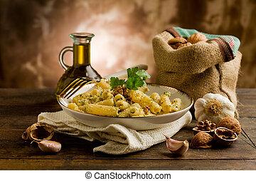 Italian regional dish made of pasta with walnut pesto on wooden table