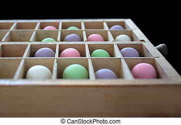 pastel balls in a type case