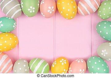 Pastel Easter egg frame against a pink wood background