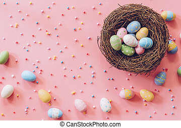 Pastel Easter eggs on pink background top view with natural light. Flat lay style.