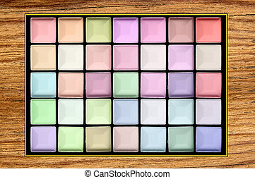pastel eyeshadows on wooden texture close-up