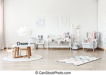 Pastel kid's room with table - Pink blanket on grey armchair...