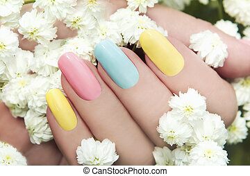 Pastel manicure. - Pastel manicure on female hand with...