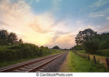 pastel sunset with railway track in a rural landscape