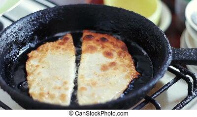 Pasties cheburek with meat fried in sunflower oil in frying pan