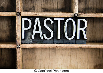 """The word """"PASTOR"""" written in vintage metal letterpress type in a wooden drawer with dividers."""