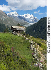 beautiful alpine landscape, wooden chalet in the Swiss Alps with views of snowy peaks