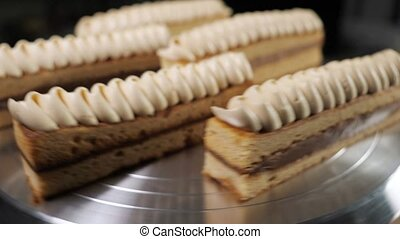 Pastries with condensed milk and cream on rotating cake...