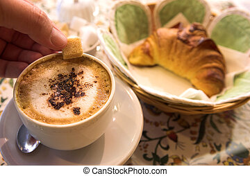 Coffee and Croissant in a French Patisserie. Man's hand holding sugar cube - Focus on Coffee