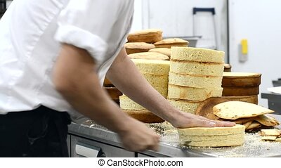 pastry chef cutting the sponge cake on layers. Cake...