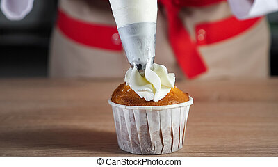 Pastry chef decorates muffin in paper cups white cream with pastry bag.