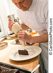 Pastry chef decorating cake with frosting in the kitchen