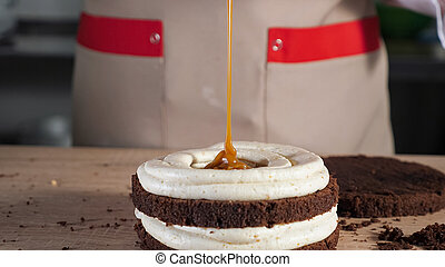 Pastry chef is pouring caramel on chocolate sponge cake. Making cake in bakery.