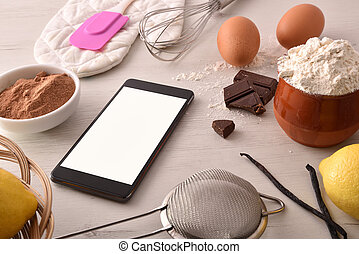 Pastry ingredients on white wooden table and mobile elevated