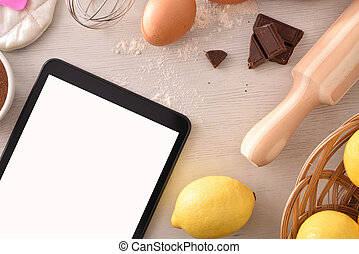 Pastry ingredients on white wooden table and tablet top