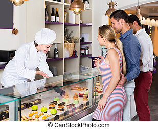 Pastry woman is serving visitors in cozy pastry shop.