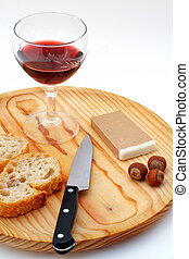 Pate, bread, glass of red wine, hazelnuts and knife a wood plate on white background