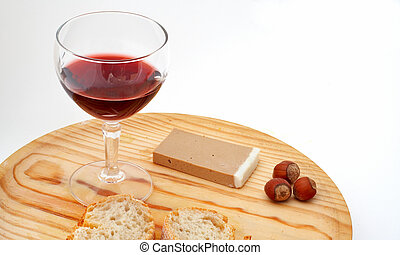 Pate, bread, glass of red wine, hazelnuts on wood plate