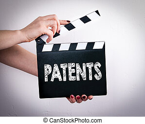 Patents. Female hands holding movie clapper