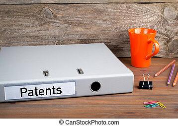 Patents. Folder, Coffee Mug, colored pencils on wooden office desk