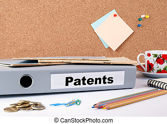 Patents. Folder on office desk. Money, Coffee Mug and colored pencils