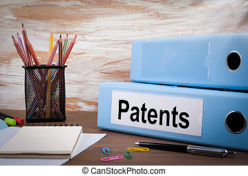 Patents, Office Binder on Wooden Desk. On the table colored pencils, pen, notebook paper