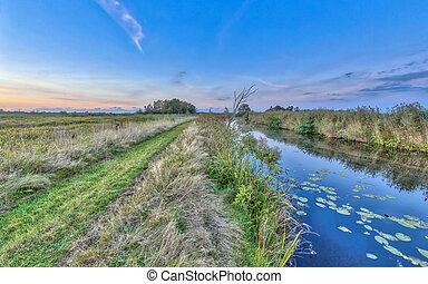 Path by river in Onlanden Nature reserve waterlogging area Groningen, Netherlands