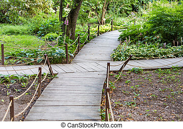 Wooden path for walking pedestrians in a modern green city park