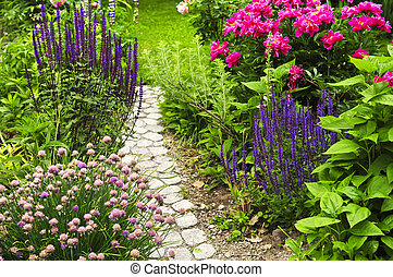 Path in blooming garden - Lush blooming summer garden with ...