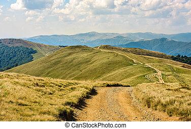 path through a meadow on mountain ridge - winding path...