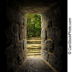 Path through trees as viewed out of a castle-like stone...