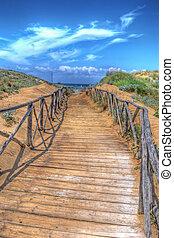 wooden boardwalk heading to the beach. Shot in Sardinia, Italy