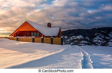 wooden chalet in deep snow at sunrise - path to wooden...
