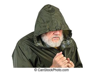 pathetic senior man in green waterproof jacket