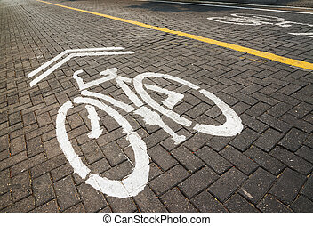 Pathway for bicycle with white bicycle lane sign on road