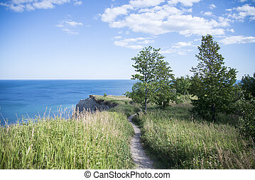 Pathway to preicpice cliff edge, overlooking vast blue water...